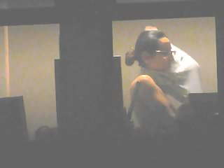 Voyeur camera vid of a topless brunette in the window
