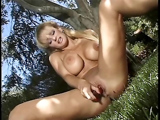 Blonde with silicone tits and hooker shoes strips outdoors and poses